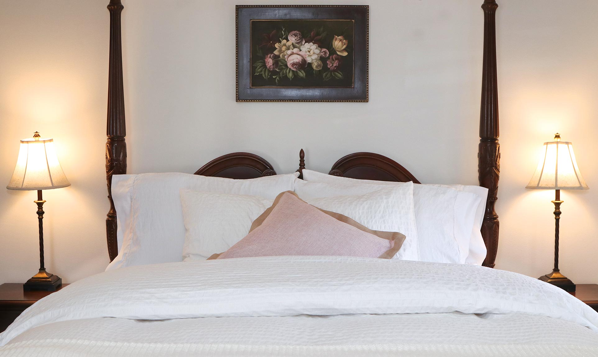 Queen size bed with two lamps on side tables flanking the bed