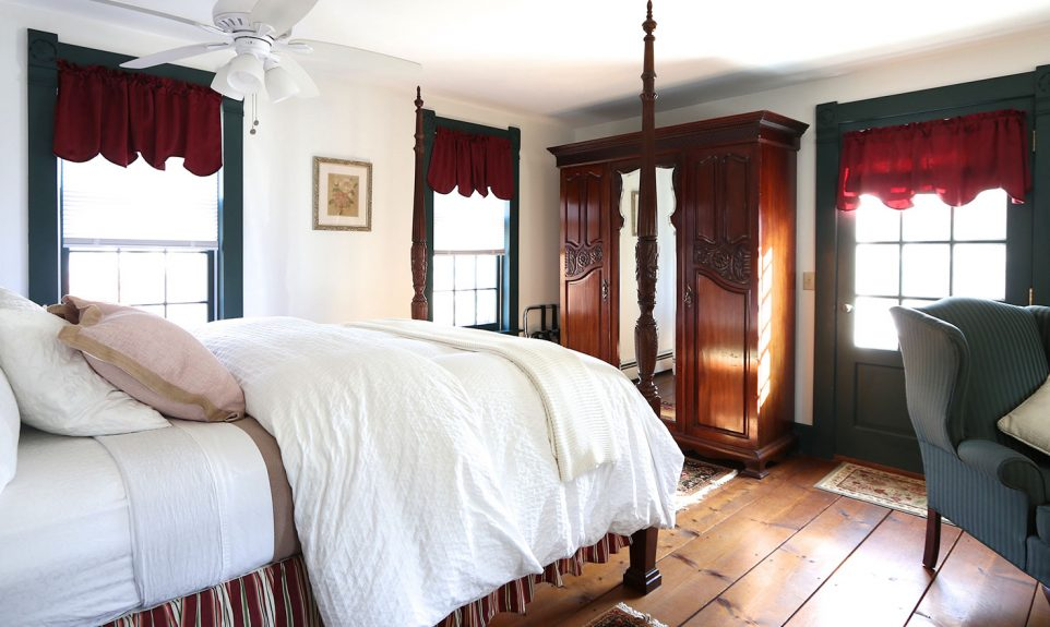 Four poster queen bed in a well lit room