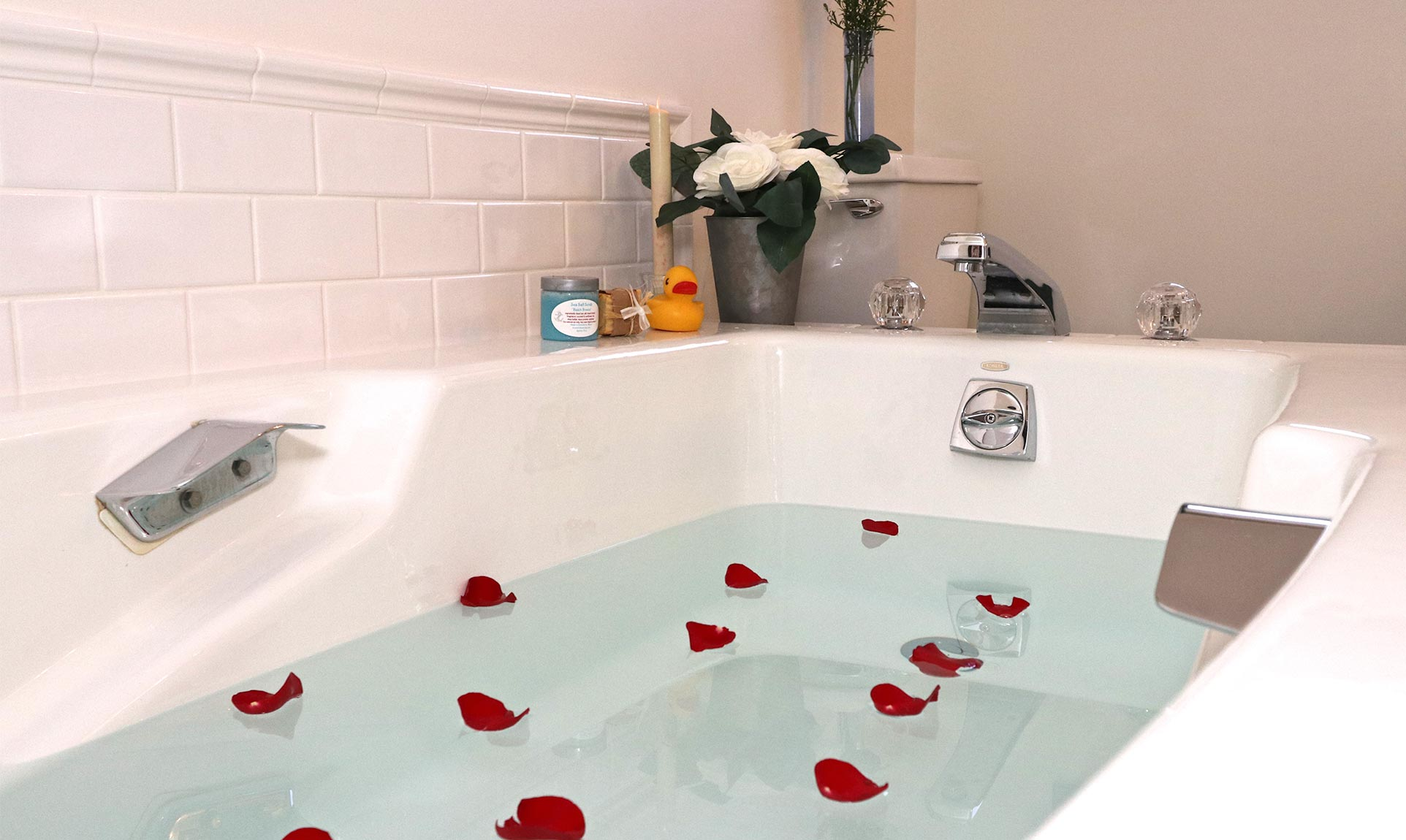 A large soaking tub filled with water and rose petals