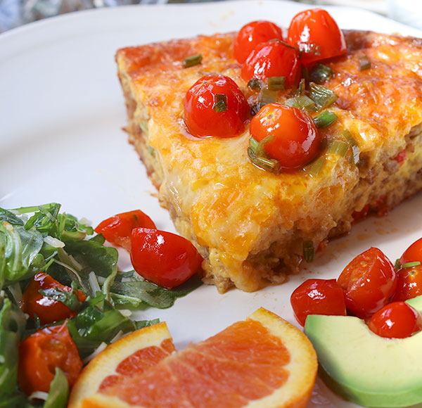 frittata served with salad and slices of avocado and oranges