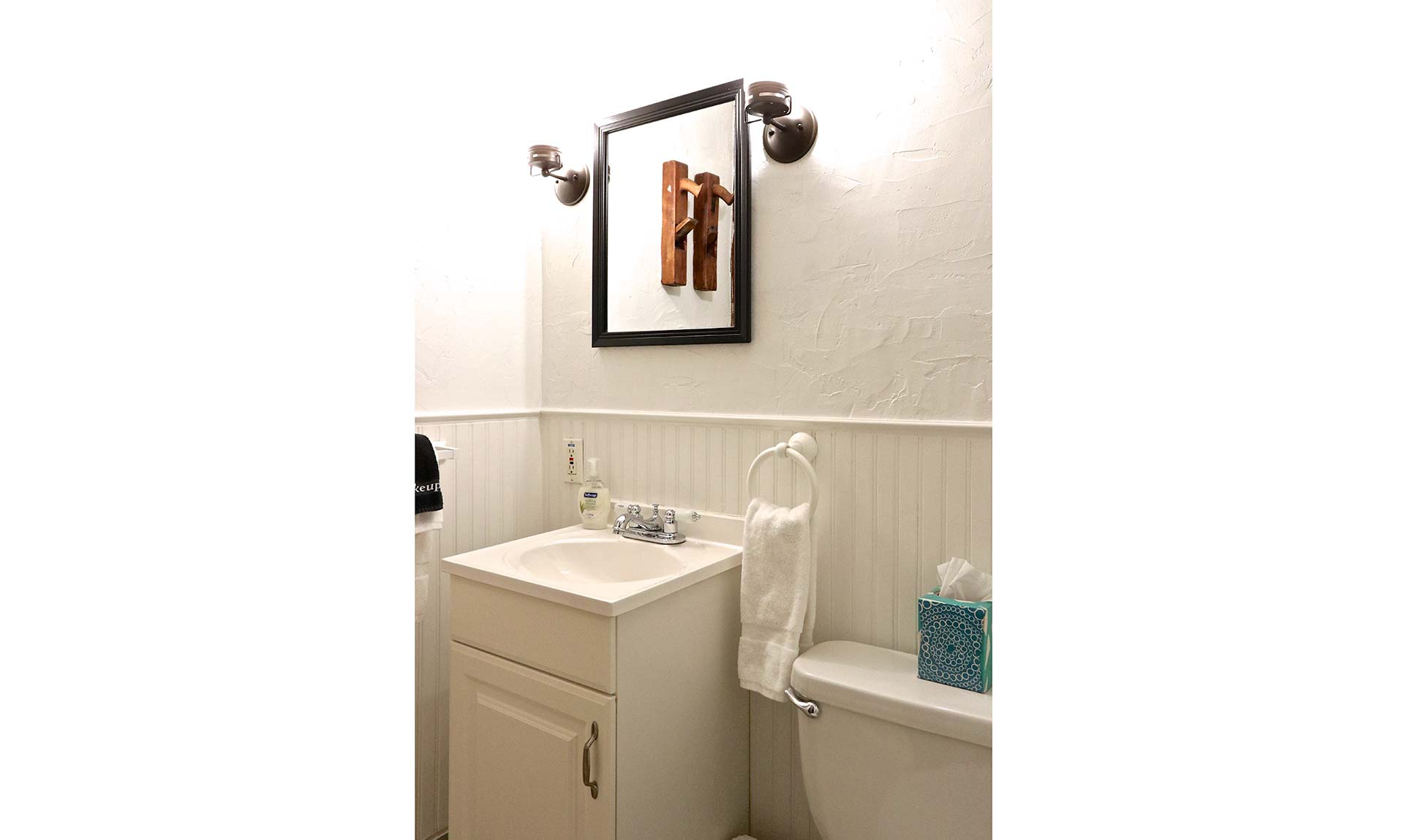 A bathroom with a small sink and mirror