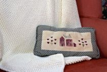 A red chair draped with a white knitted blanket and a pillow with an embroidered barn