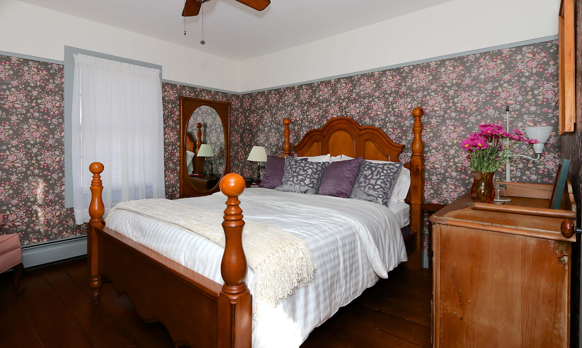 Queen bed in a room with a ceiling fan
