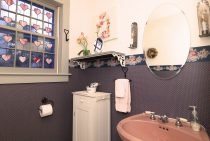 Bathroom with pink sink and purple wallpaper with flowers in a vase