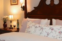 Queen bed with lamp and two wine glasses on an end table