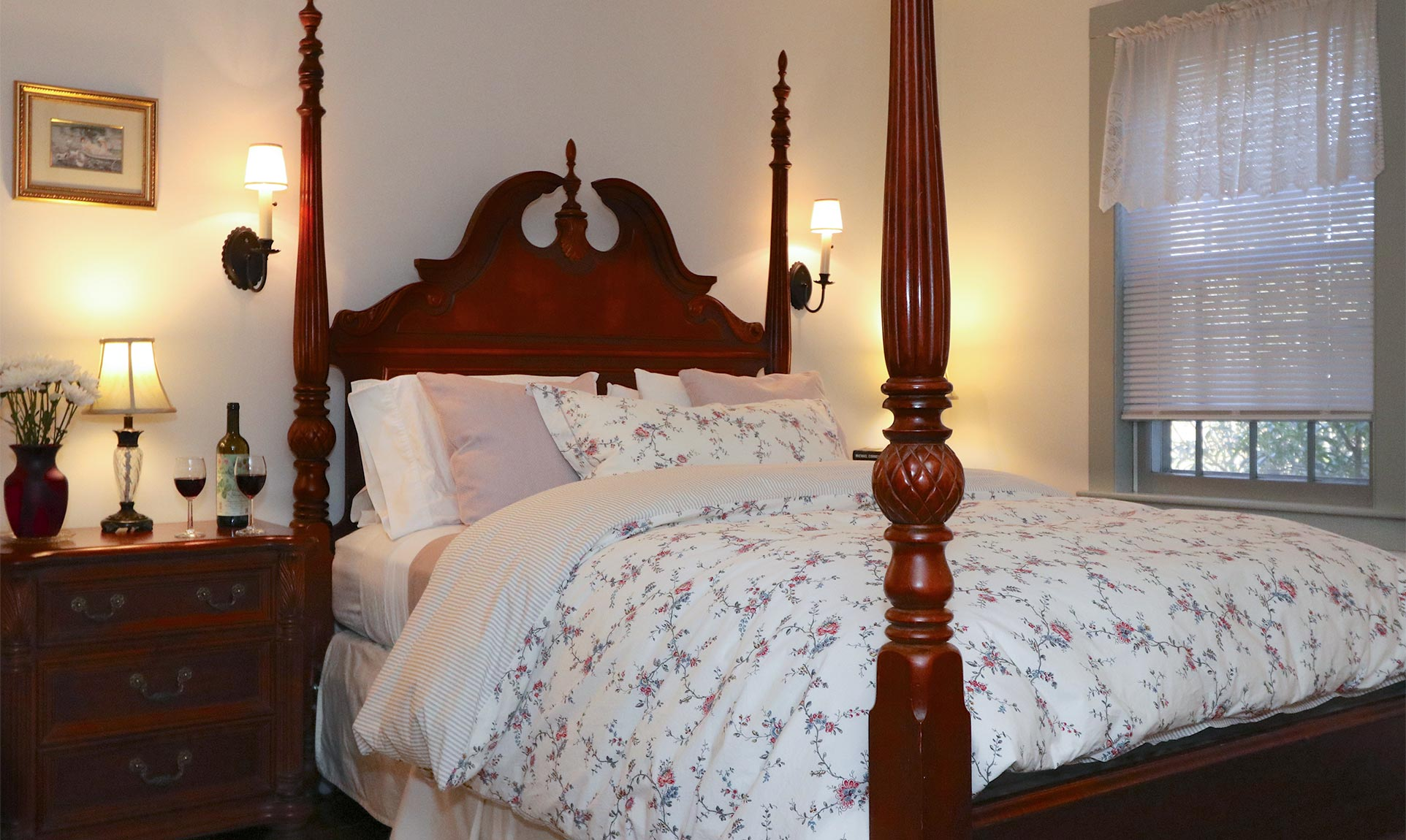 Four poster queen bed in a room with side tables and lamps