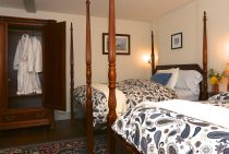 Two double beds and an antique armoire with white bath robes
