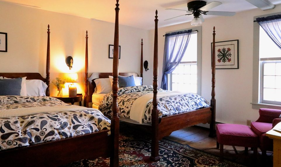 Two four poster double beds in a room with a room with natural light