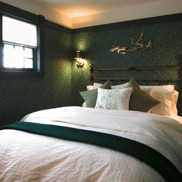A queen bed in a room with green and gold wall paper