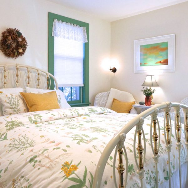 A bed in a well lit room with white walls and green trim