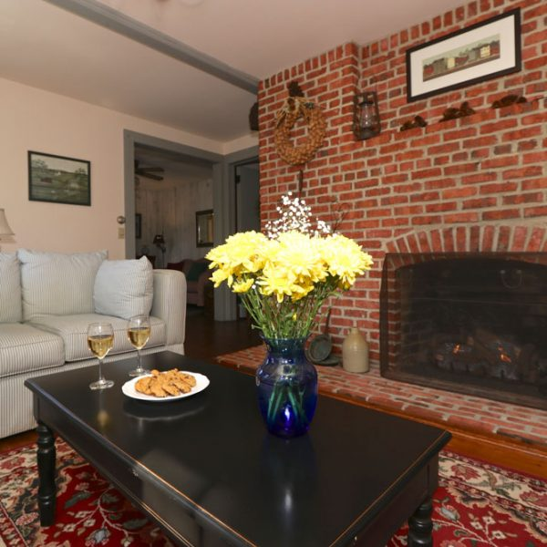 A large living room with couches, coffee table and a large brick fire place