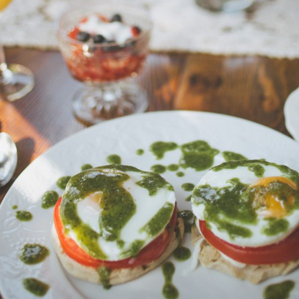 A breakfast of toast, tomatoes, and egg topped with a drizzle of pesto served with fresh fruit