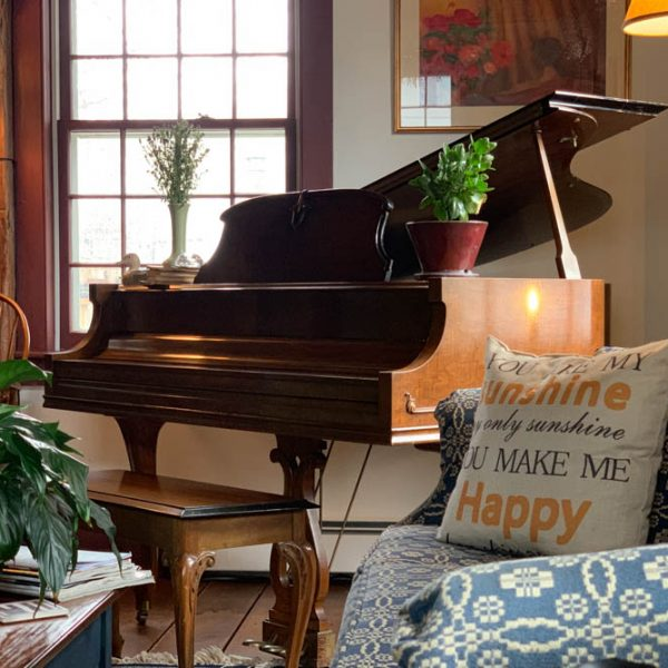 A cozy living room with a piano in the corner