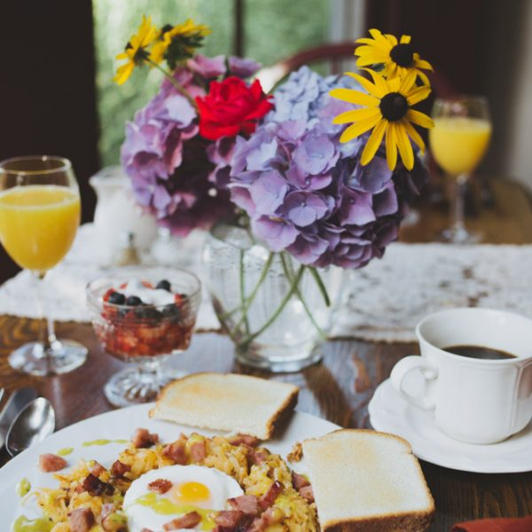 Breakfast of egg, potatoes, and sausage, served with coffee, orange juice, fruit on a table with flowers