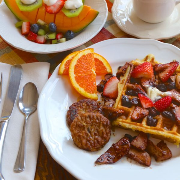Breakfast of waffles served with fresh fruit, sausage, and orange slices