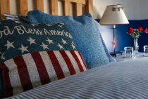 American flag decorative pillow on a bed with a lamp on an end-table