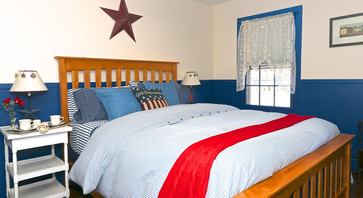 Queen bed in a room with Americana decorations
