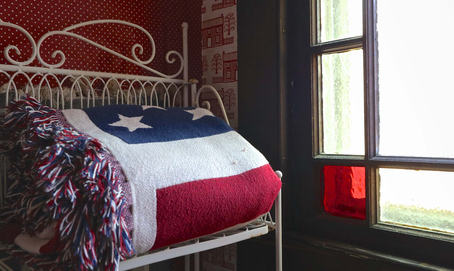 A wire table with a folded American flag blanket near a stained glass window