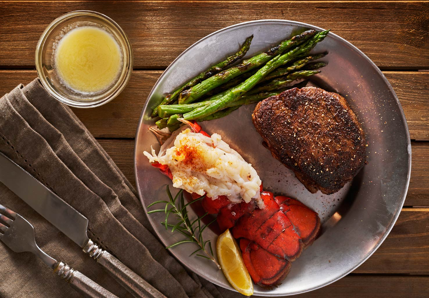 Steak and a lobster tail with asparagus and butter