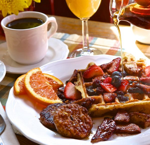 Waffles with fresh fruit, sausage, and orange slices