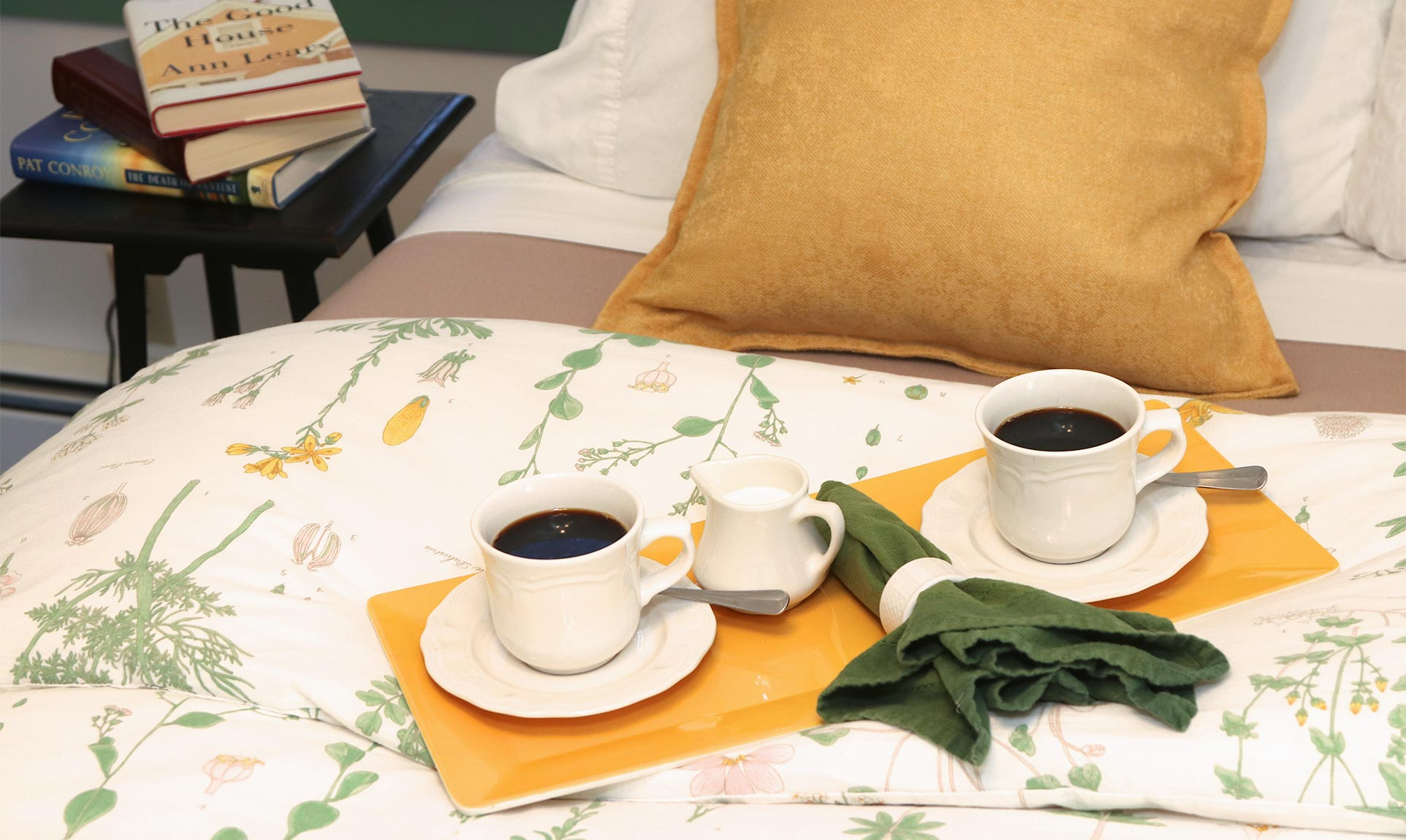 Two cups of coffee on saucers on a bed