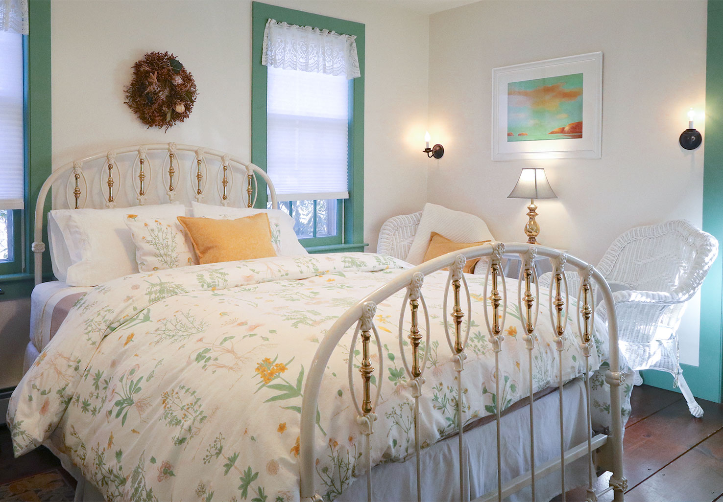 Queen bed in a room with white chairs and a door to a private balcony