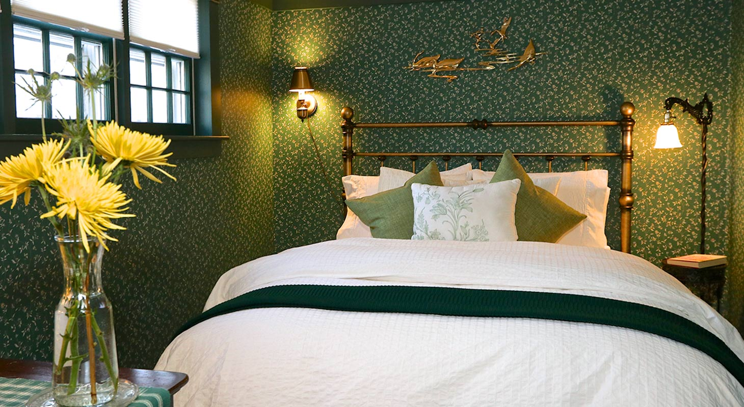 Queen bed with a vase and yellow flowers in a room with green floral wallpaper