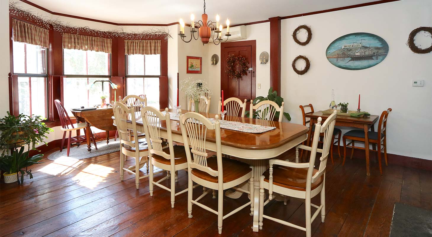 Eight person dining table in a spacious room with bay windows