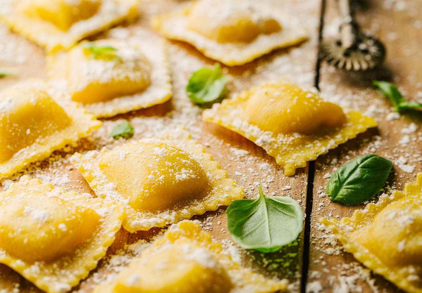 Wooden table with fresh made ravioli and basil leaves