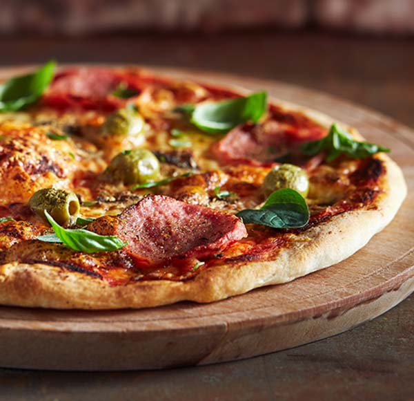 Thin crust pizza with basil and pepperoni
