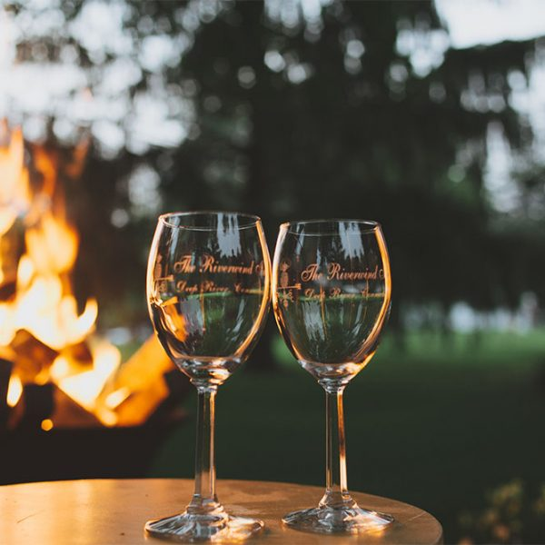two glasses of wine on a table in front of a outdoor fire pit